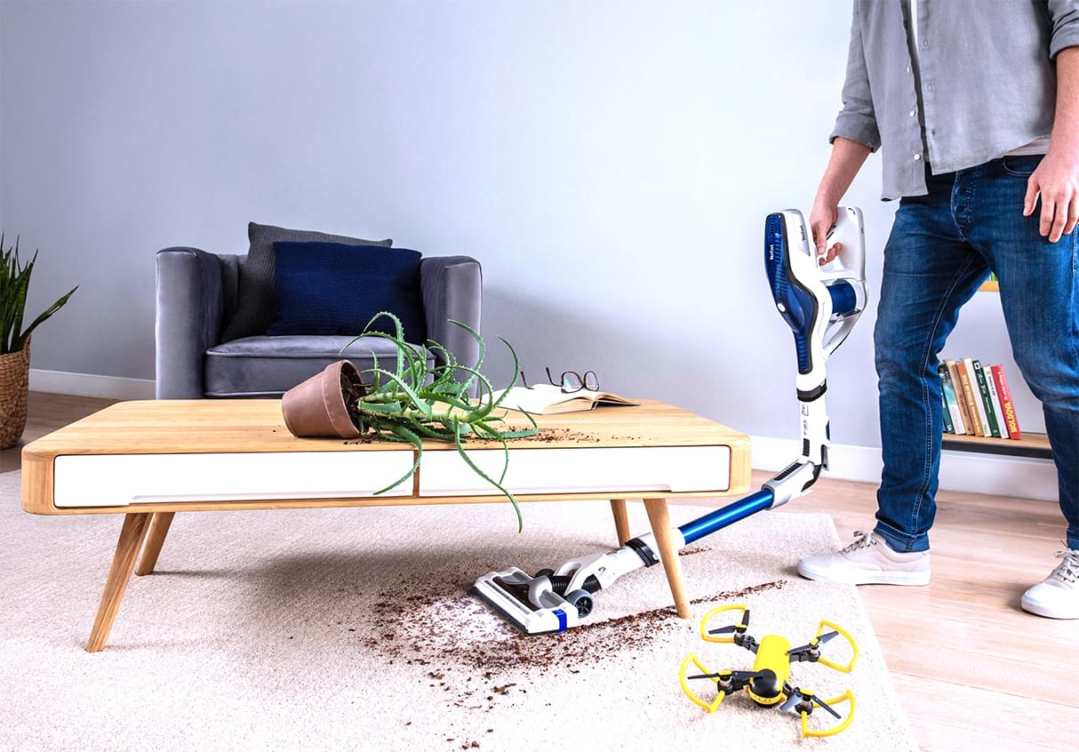 Man vacuuming under a brown table