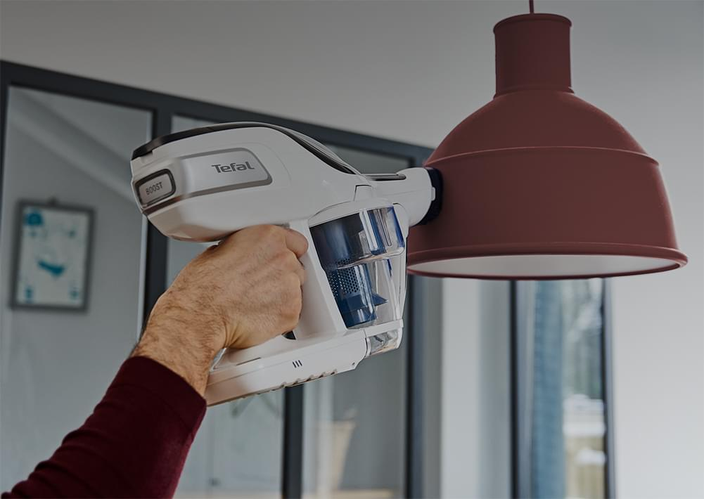 Man vacuuming on a lamp