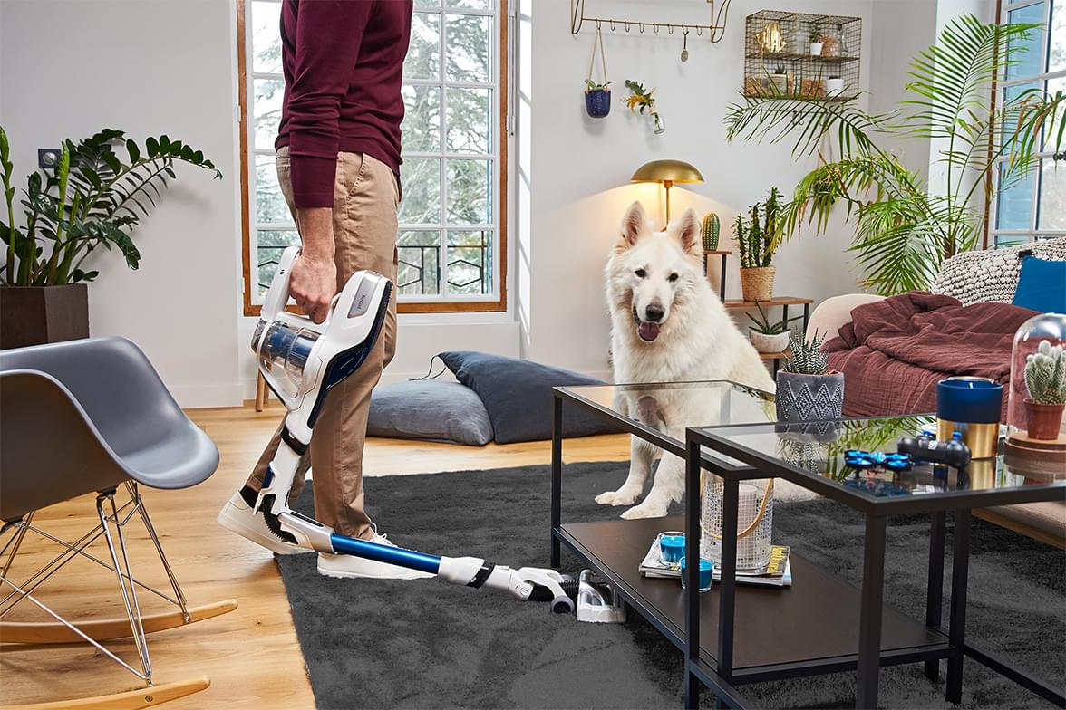 Man vacuuming in front of his dog